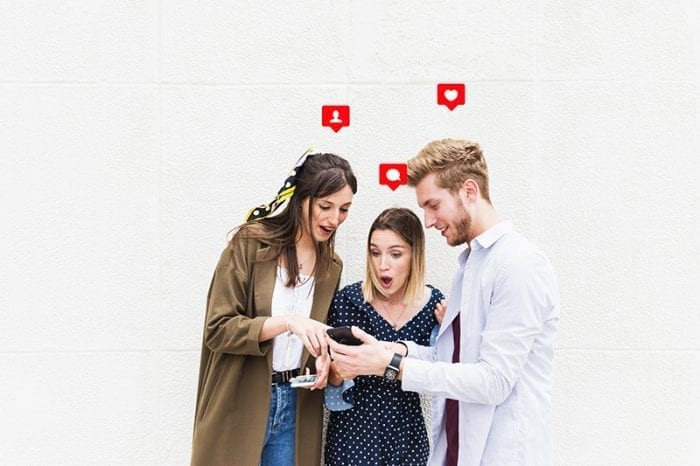 A man showing his smartphone to two girls with a wow reaction